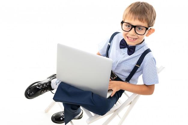 Menino de escola adolescente fazer lição de casa com laptop, isolado