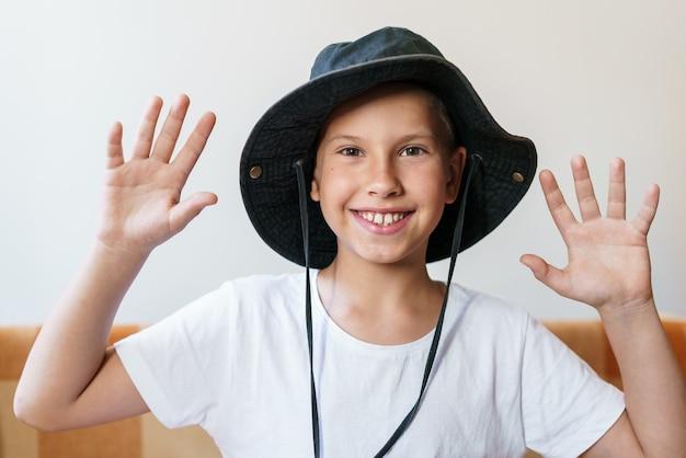 Menino de escola alegre sorrindo enquanto olha para a câmera em uma camiseta branca e um chapéu de sol preto cau ...