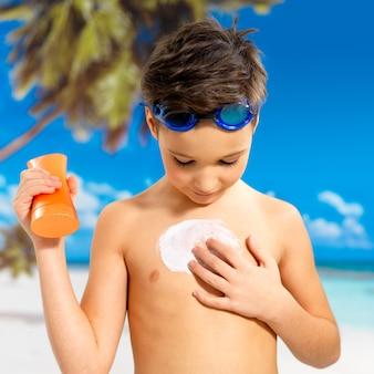 Menino de escola aplicando creme protetor solar no corpo bronzeado. menino segurando o frasco de loção laranja bronzeador.