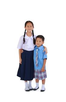 Menino de escola asiática e menina em pé de uniforme escolar tailandês se abraçam isolados no fundo branco. comprimento total com caminho de recorte