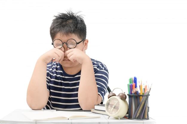 Menino de escola asiática esfregando os olhos isolados