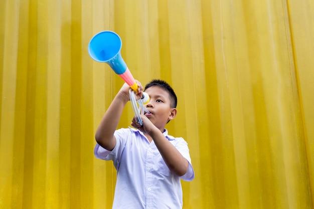 Menino de escola asiática que funde um chifre colorido no fundo amarelo.