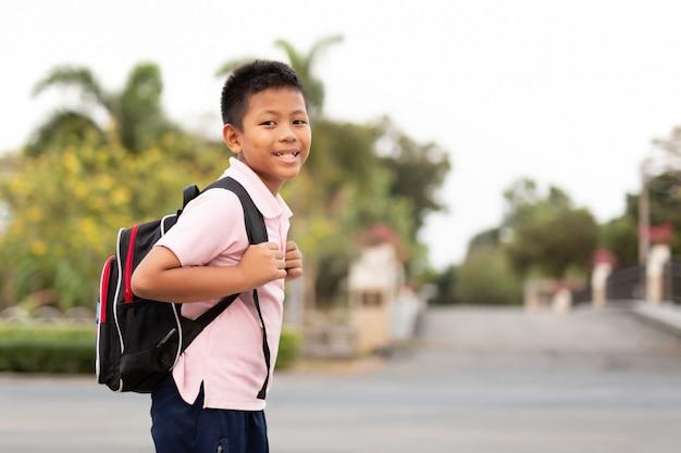 Menino de escola asiático feliz no uniforme com trouxa que anda para trás em casa.