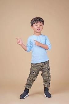 Menino de escola bonito bonito asiático, animado com gestos com os dedos