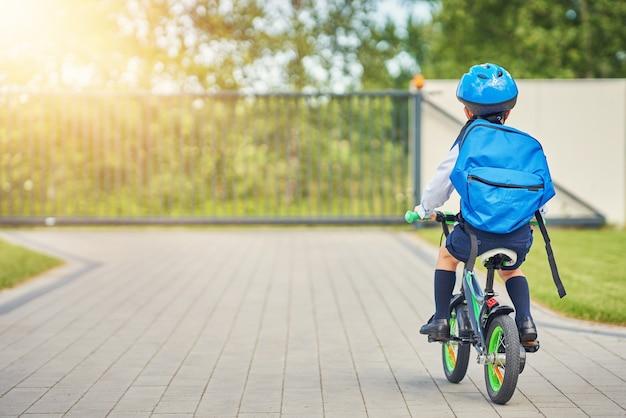 Menino de escola com capacete de segurança andando de bicicleta com mochila
