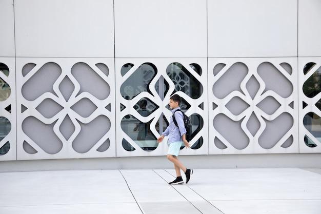 Menino de escola com mochila caminha na parede de concreto do edifício. copie o espaço