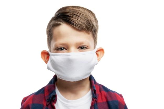 Menino de escola com uma máscara médica. fechar-se. isolado em um fundo branco.