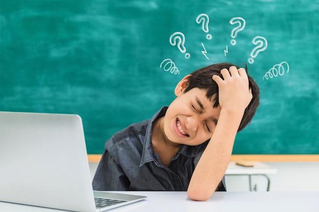 Menino de escola confuso asiático que usa o laptop no fundo preto da placa com sinal cansado e do ponto de interrogação.