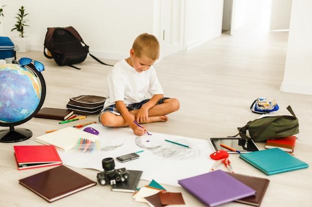 Menino de escola de desenho enquanto está sentado no chão