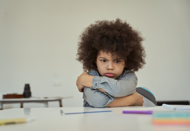 Menino de escola descontente com cabelo afro parecendo ressentido franzindo a testa enquanto está sentado com os braços