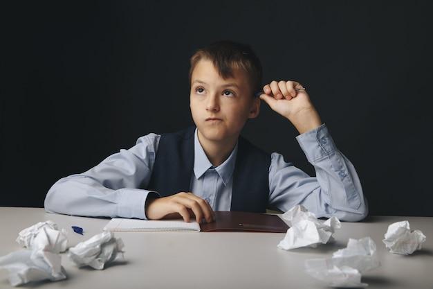 Menino de escola doente e cansado sentado à mesa e estudando.