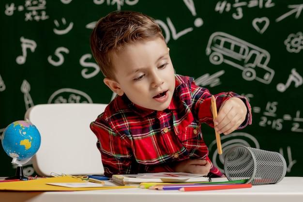Menino de escola emocional sentado na mesa com muitos materiais escolares. primeiro dia de aula. garoto garoto da escola primária. de volta à escola. criança do ensino fundamental.