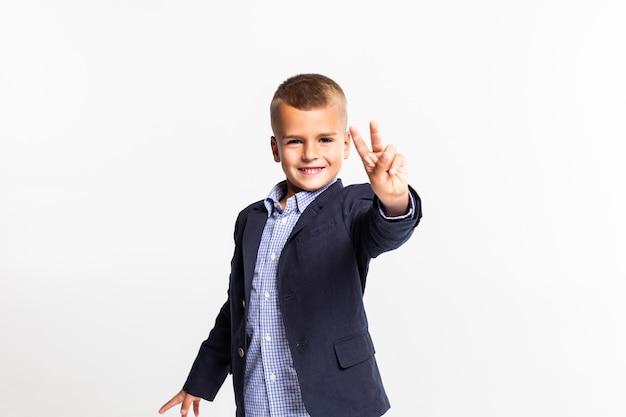 Menino de escola engraçado mostrando sinal de vitória no olho, isolado na parede branca.