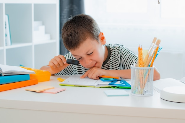 Menino de escola está sentado em casa à mesa e resolvendo a lição de casa olhando através de uma lupa. volta às aulas, preparação, educação em casa.