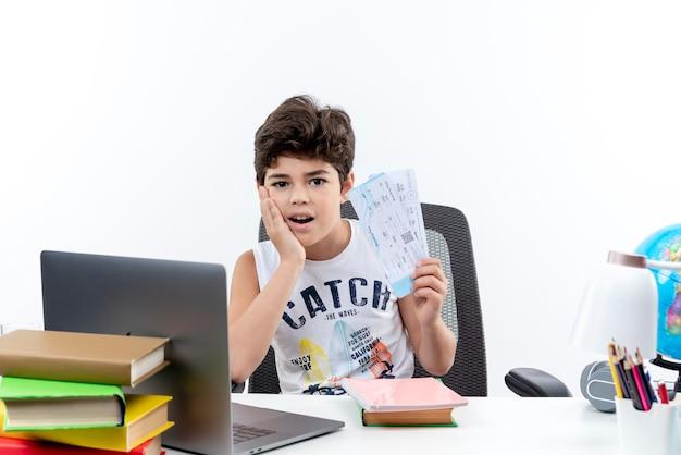 Menino de escola impressionado sentado na mesa com as ferramentas escolares, segurando ingressos e colocando a mão na bochecha