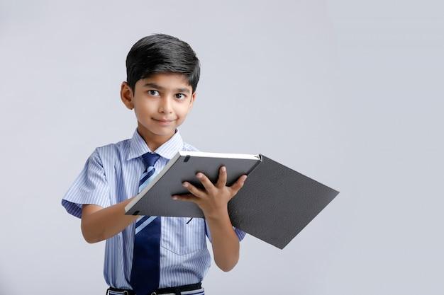 Menino de escola indiano / asiático com caderno e estudar