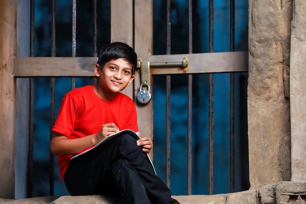 Menino de escola indiano com caderno e estudando em casa