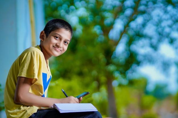 Menino de escola indiano dando aula de ensino à distância por telefone usando aplicativo móvel, assistindo a aula on-line, fazendo videochamadas no aplicativo, fazendo anotações, estudando em casa