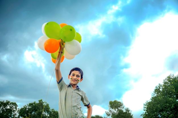 Menino de escola indiano pulando no céu com balões tricolores e celebrando o dia da independência ou da república da índia