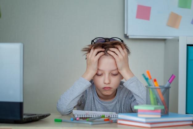 Menino de escola infeliz e estressado, estudando com um caderno em sua mesa em casa. a criança está cansada de aprender online. conceito de educação e infância