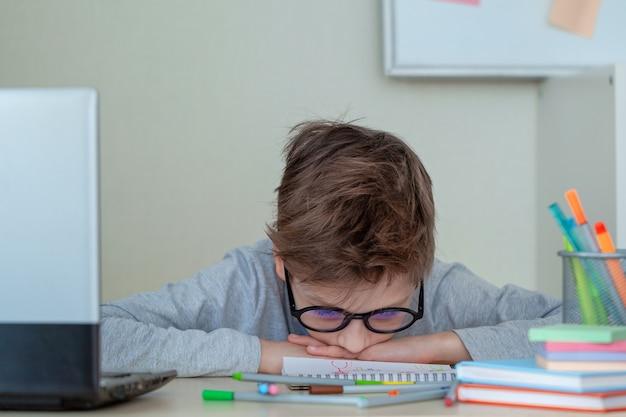 Menino de escola infeliz e estressado, estudando com um caderno em sua mesa em casa. a criança está cansada de aprender online. criança descansa de bruços na mesa. conceito de educação e infância