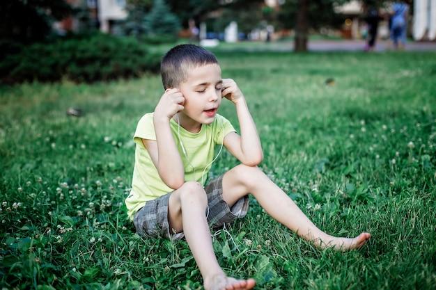 Menino de escola legal com fones de ouvido na rua