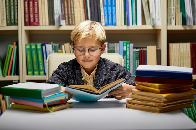 Menino de escola lendo livro enquanto se prepara para a aula na biblioteca, criança diligente e tímida está concentrada na leitura