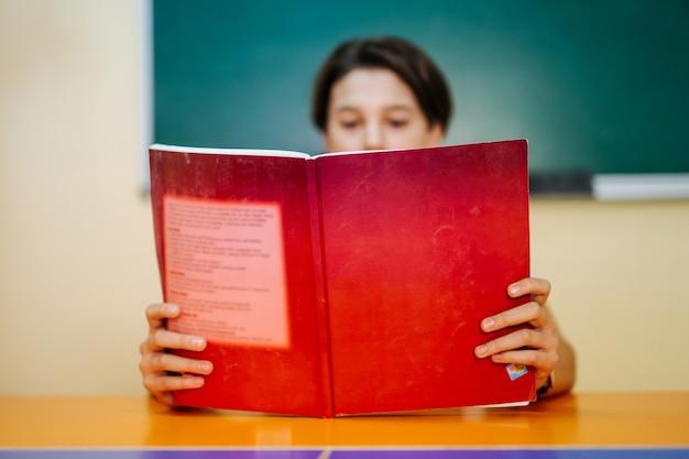 Menino de escola lendo na aula. grande livro de texto vermelho na vista frontal.