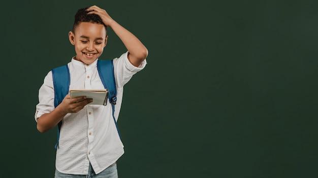 Menino de escola lendo suas anotações copiar espaço