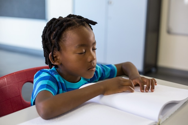 Menino de escola memorizando a lição em sala de aula