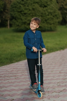 Menino de escola, montando uma scooter no parque