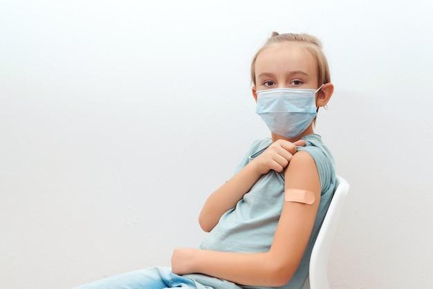 Menino de escola na máscara facial mostrando o braço com bandagem. injeção de vacina no ombro. menino recebendo a vacina. campanha de vacinação contra o coronavírus. conceito de infância e infecção.
