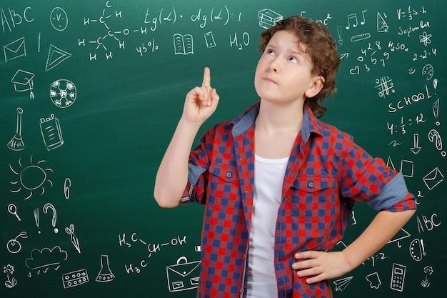 Menino de escola pensativo alegre, volta ao conceito de escola