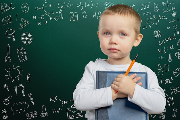 Menino de escola pensativo alegre, volta às aulas