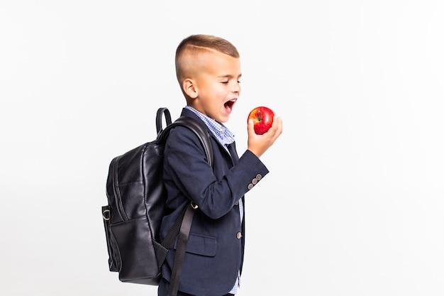 Menino de escola pequena com saco se preparando para morder uma grande maçã vermelha e pé isolado na parede branca