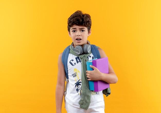 Menino de escola preocupado com uma bolsa nas costas e fones de ouvido segurando livros isolados em fundo amarelo