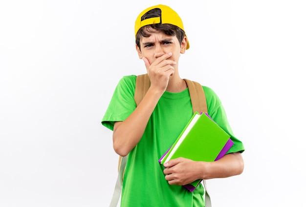 Menino de escola preocupado usando uma mochila com tampa, segurando livros, tapando a boca com a mão isolada na parede branca