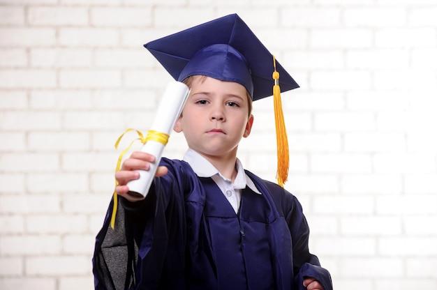 Menino de escola primária em copo e vestido posando com diploma.