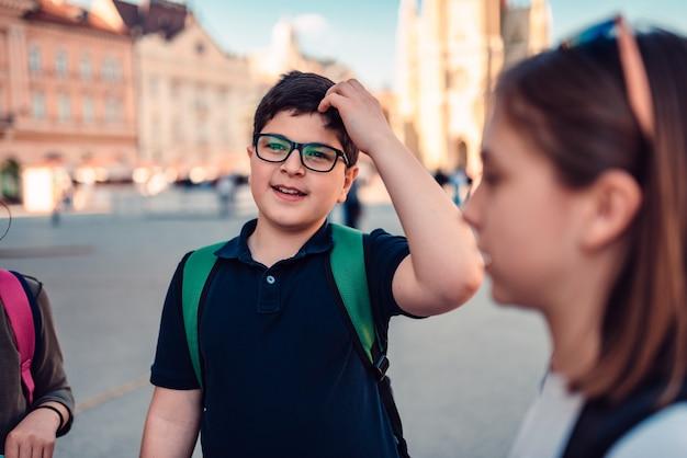 Menino de escola sair com amigos e coçar a cabeça