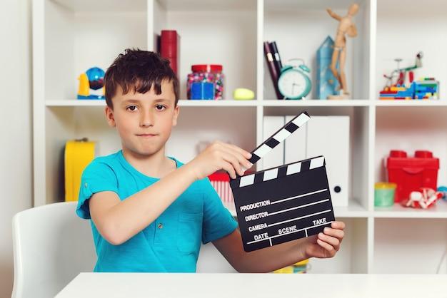 Menino de escola segurando um filme preto fazendo claquete. produtor fazendo filme. nova ideia para projeto escolar.