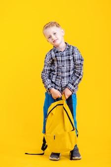 Menino de escola segurando uma bolsa sorrindo