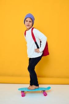 Menino de escola sorridente andando de skate com um chapéu azul de fundo amarelo