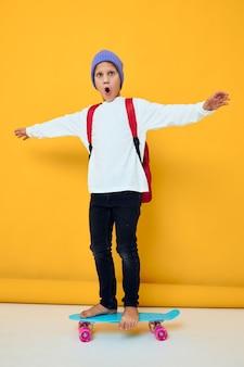 Menino de escola sorridente andando de skate em um estilo de vida de estúdio de chapéu azul