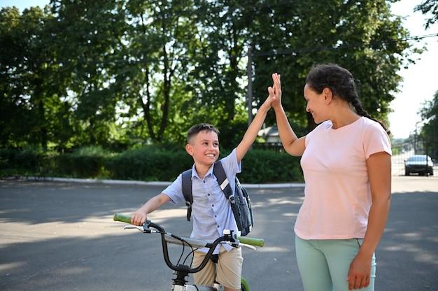 Menino de escola sorridente dando high five para sua mãe afro-americana. criança voltando para a escola. crianças de bicicleta