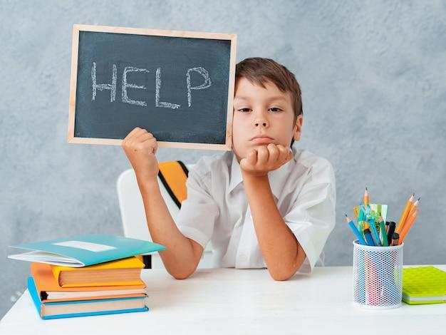 Menino de escola triste cansado e frustrado na mesa e segurando o papel com a palavra ajuda a aprender difficulti ...