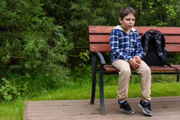 Menino de escola triste com mochila sentado em um banco da rua e pensando