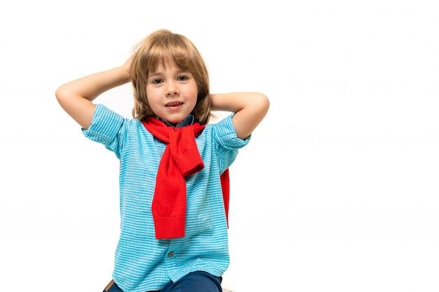 Menino de esportes em t-shirt com capuz em volta do pescoço gesticula isolado em azul