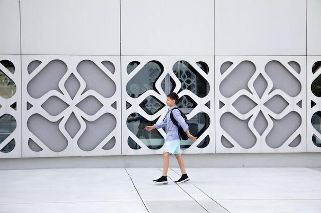 Menino de estudante com mochila caminha na parede de concreto do edifício. copie o espaço para o texto