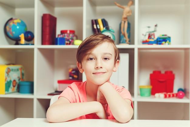 Menino de estudante feliz aprendendo no conceito de infância e pessoas em casa.