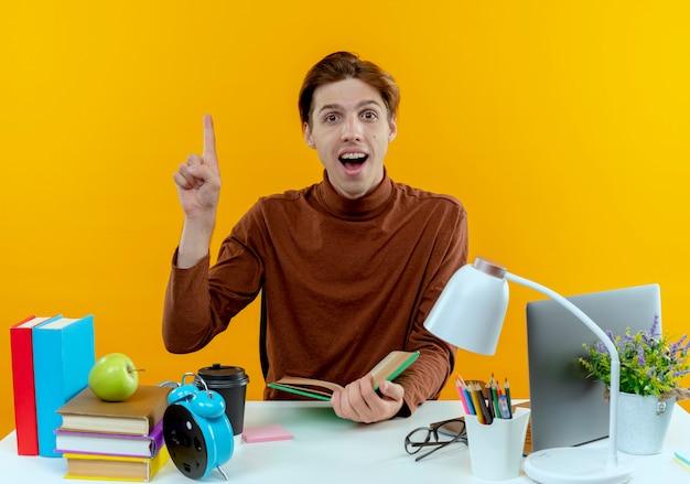 Menino de estudante surpreso sentado na mesa com ferramentas escolares segurando um livro e aponta para cima em amarelo